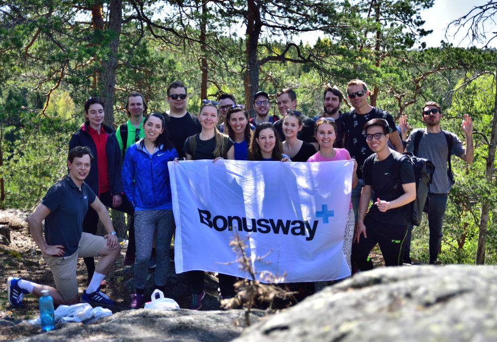 Group of people posing with a sheet of material reading Bonusway