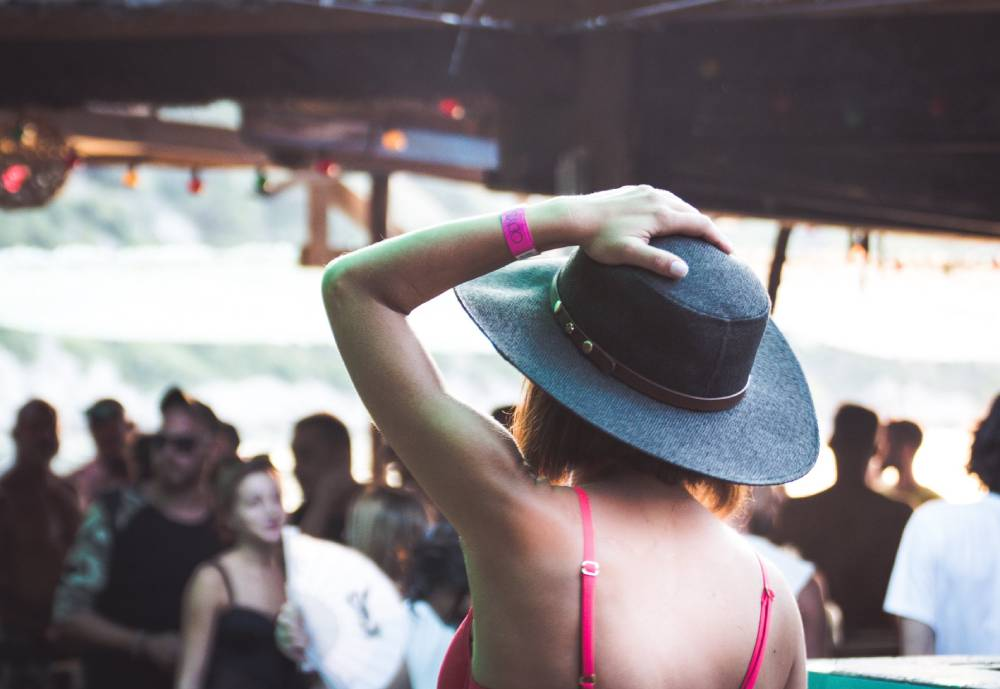 woman holding her hat at an outdoors party