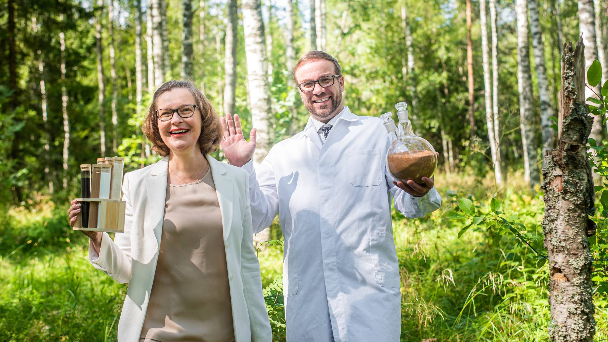 A man and woman standing in a forest in laboratory attire with laboratory equipment in hand.