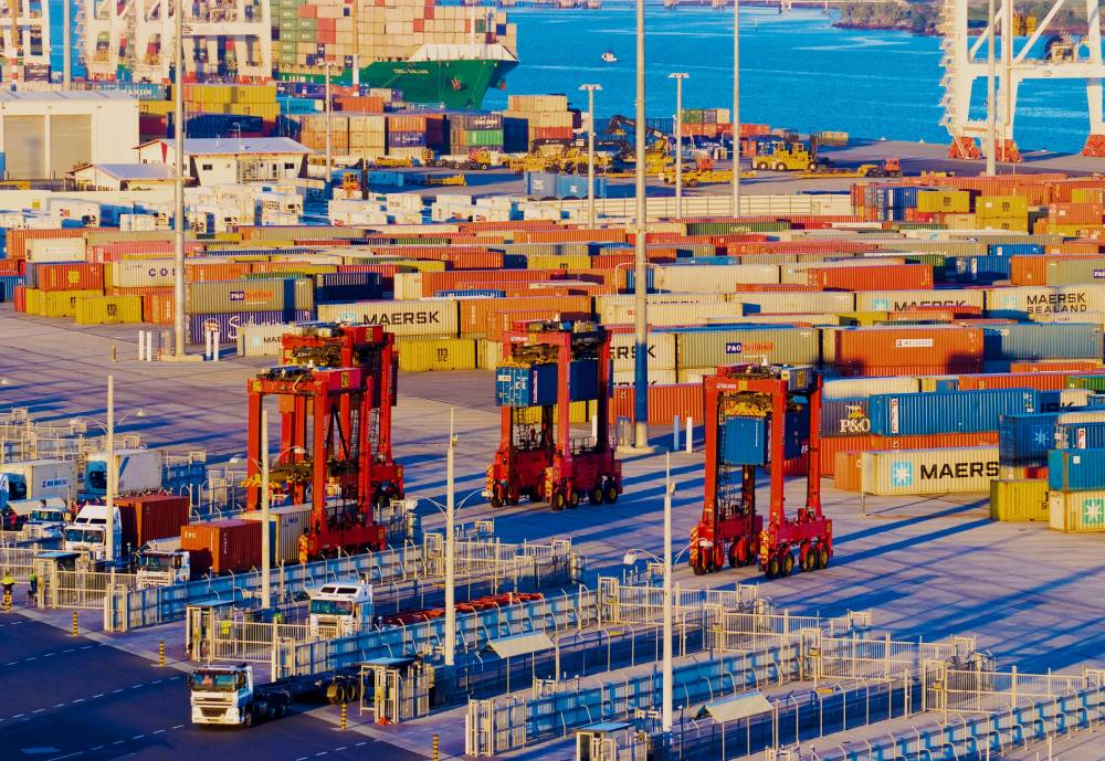 An overhead photo of a shipping containers and port equipment at a terminal.