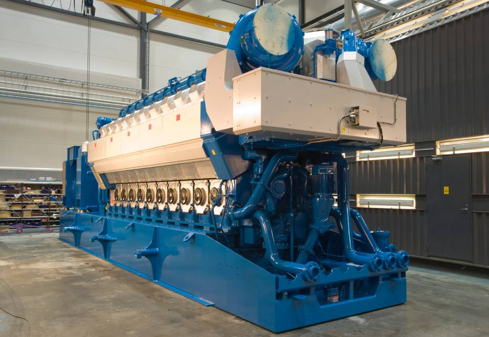 A blue-and-silver dual-fuel engine in an industrial hall.