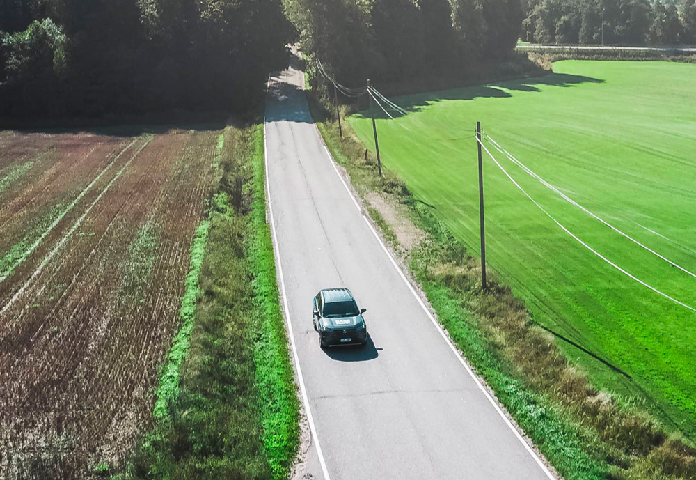 An aerial view of a car on a road in the countryside.