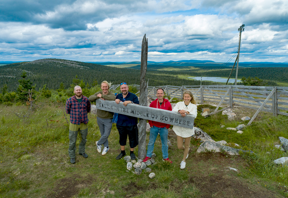 """Five people standing in the nature and leaning on a sign saying, """"Salla in the middle of nowhere"""""""