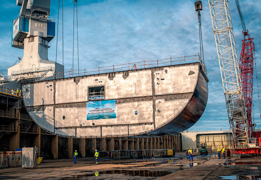 The keel of a ferry hanging over a handful of workers at a shipyard.