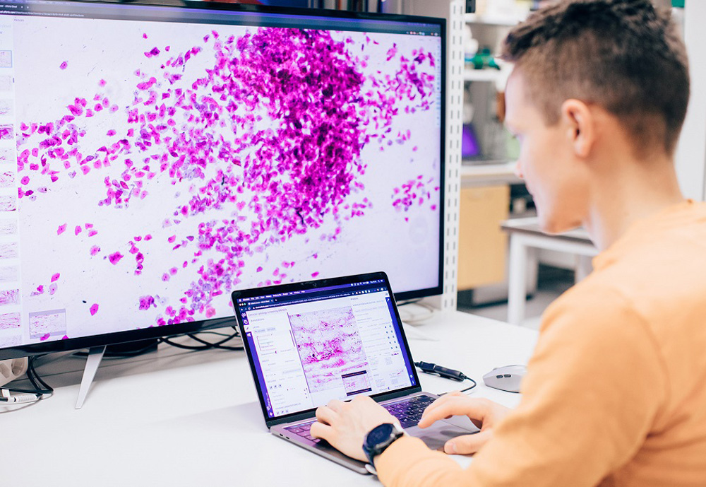 Data scientist working on computer in front of a large screen