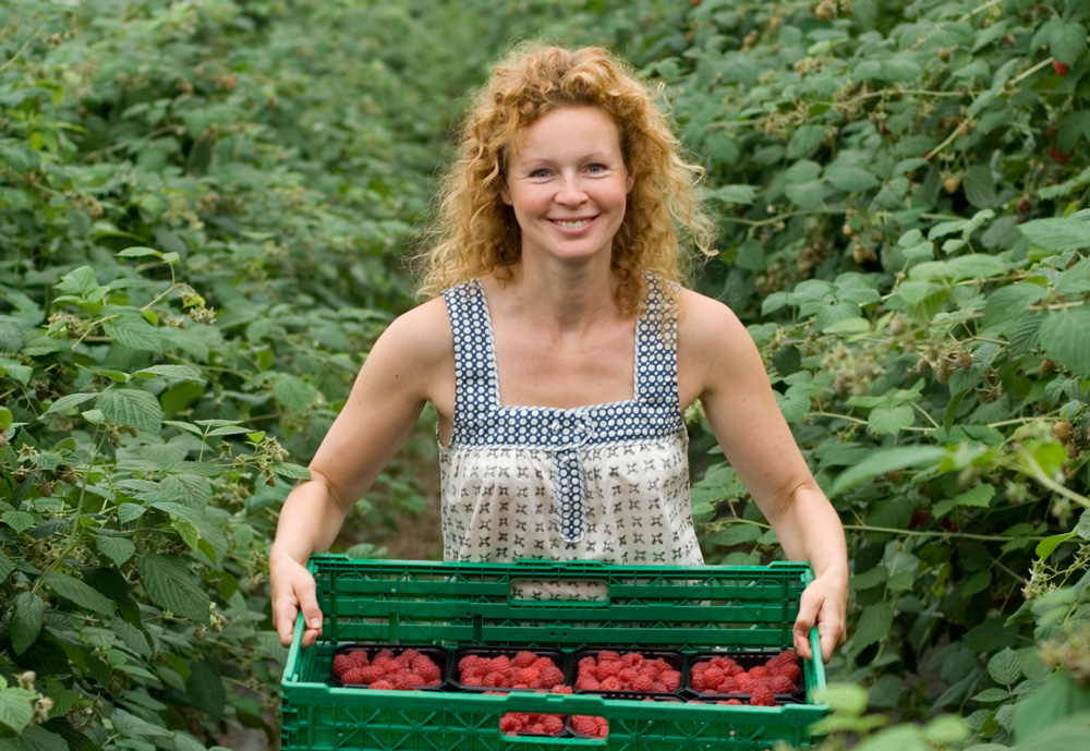 A woman holding a box with raspberries