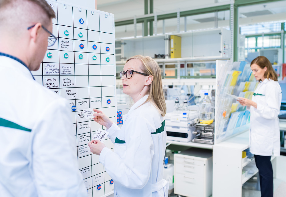 Two people in a lab having a discussion with a third person looking at papers on the background