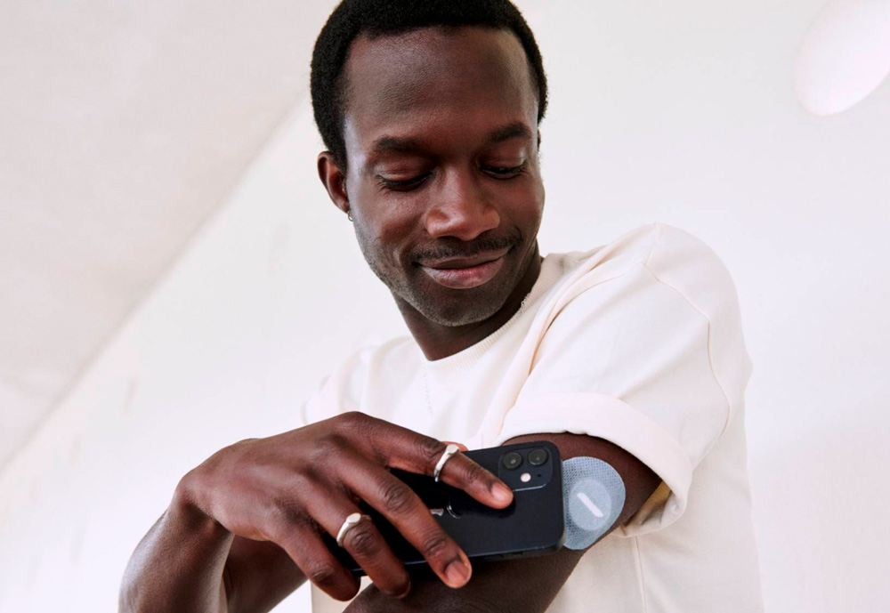 A man using mobile phone to scan a sensor patch on his arm