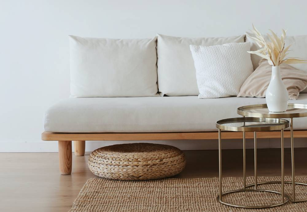 A sofa with white cushions on wooden floor.