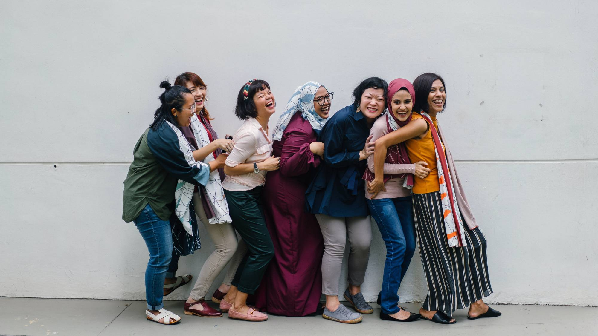 Seven women on the street laughing.